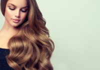 Brunette girl with long and volume shiny wavy hair . Beautiful woman model with curly hairstyle .
