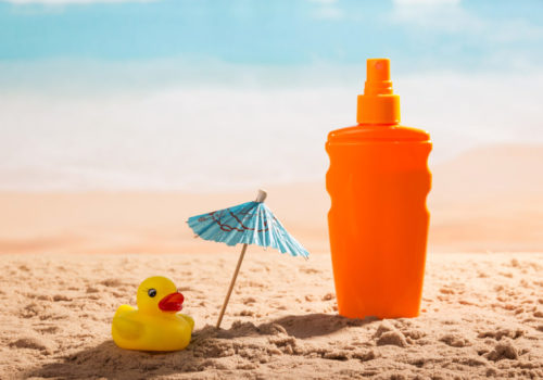 Sunscreen, umbrella and rubber duck in sand against sea.